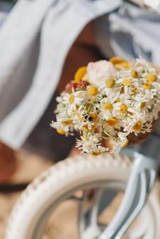 新鮮な黄色い花のクローズアップと自転車の車輪。抽象化