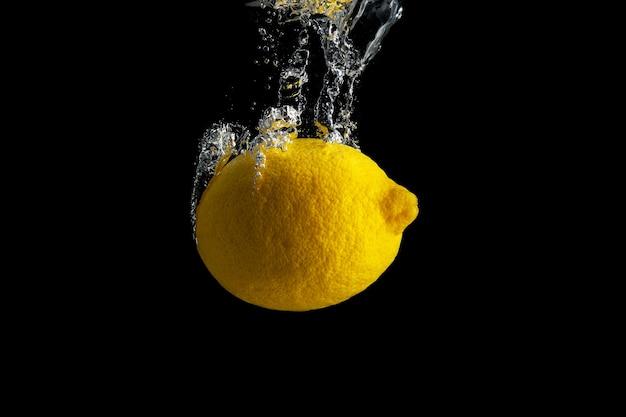 Свежий желтый лимон в брызгах воды, изолированных на черном.