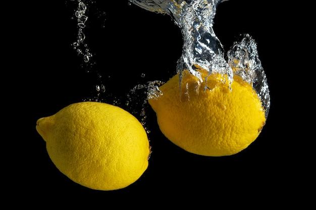 블랙에 절연 물 얼룩에 신선한 노란색 레몬.