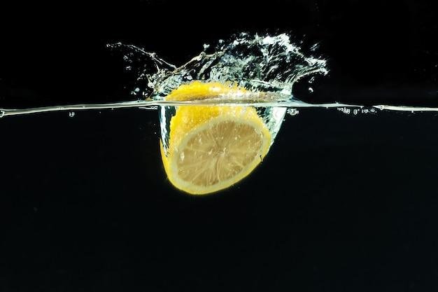 Свежий желтый лимон в брызгах воды на черном фоне