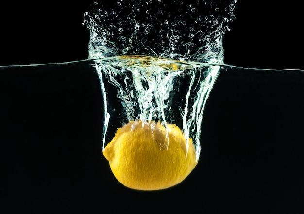 Свежий желтый лимон в плеск воды на черном фоне