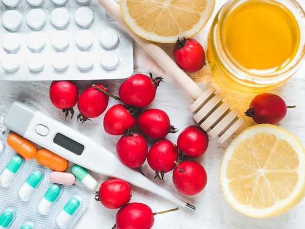 Fresh yellow lemon, jug of honey and red berries on a white wooden table. top view, close-up, isolated. concept of preventing colds