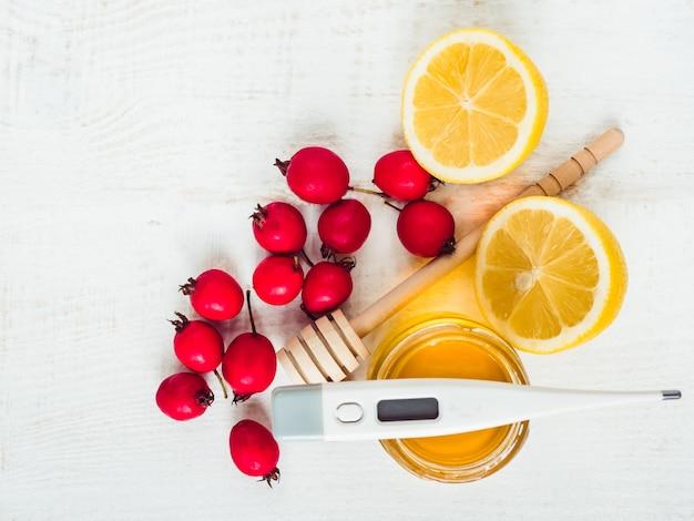 Свежий желтый лимон, кувшин меда и красных ягод на белом деревянном столе. вид сверху, крупный план, изолированные. концепция предотвращения простуды