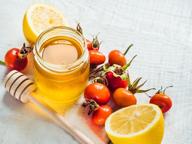 白い木製のテーブルに新鮮な黄色のレモン、蜂蜜の水差しと赤いベリー。上面図、クローズアップ、孤立。風邪予防のコンセプト