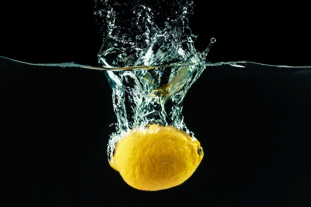 Fresh yellow lemon in water splash on black background