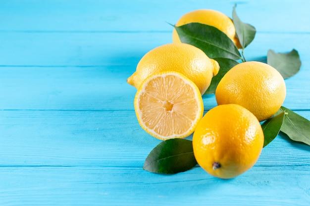 青い木製の背景に新鮮な黄色のレモン。コピースペース