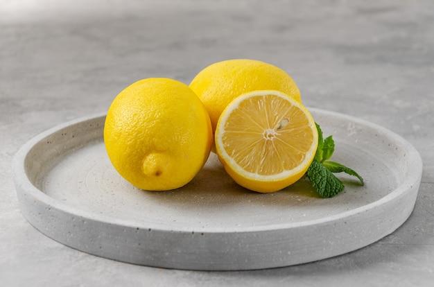 Свежие желтые лимоны на сером фоне бетона. цвет года.