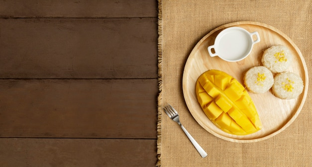 Fresh yellow mango peel and sliced cubes on wood table.