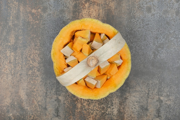 Zucca gialla fresca su fondo di marmo