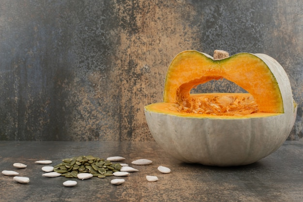 Fresh yellow pumpkin with seeds on marble surface