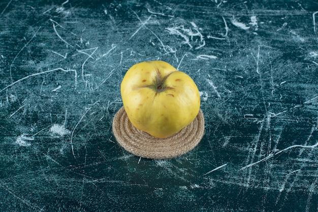 Mela cotogna gialla fresca sulla tavola di marmo.