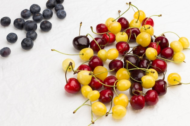 Fresh yellow and red cherry, blueberry on white surface. flat lay  copy space.
