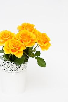 흰색 배경에 흰색 냄비에 신선한 노란 장미 꽃다발