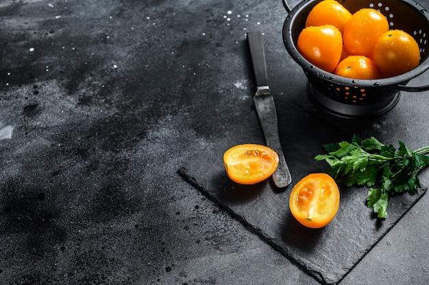 黄色いトマトを半分に切る。黒の背景