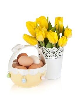 Свежие желтые тюльпаны и яйца в миске. изолированные на белом фоне