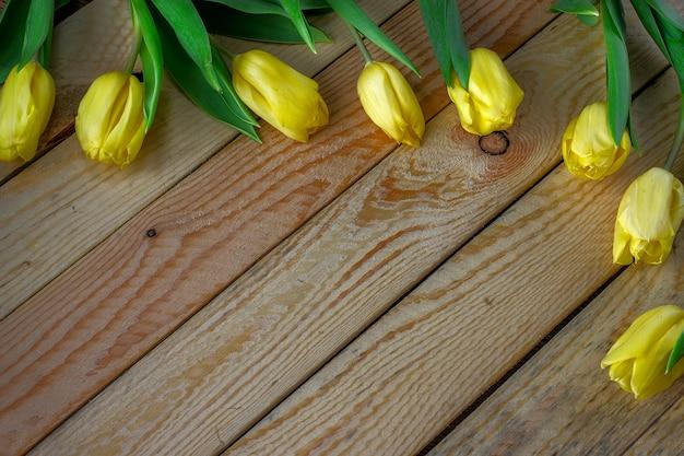 Свежие желтые тюльпаны на деревянном столе. может использоваться как фон