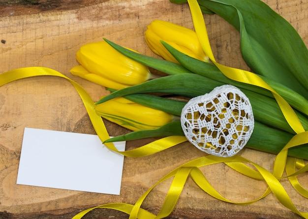 天然木の板にリボンとギフト用の箱が付いた新鮮な黄色のチューリップ。