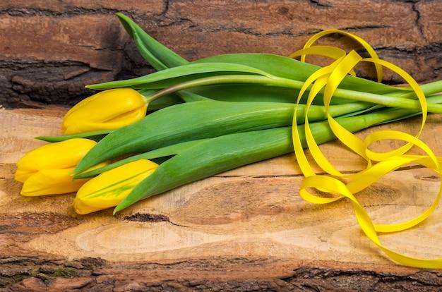 天然木の板にリボンが付いた新鮮な黄色のチューリップ。