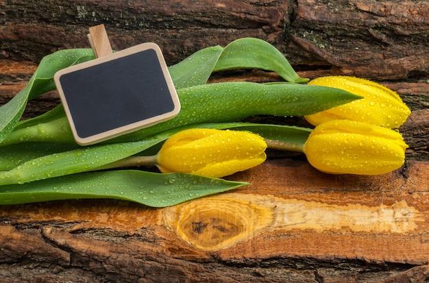 天然木の板に水滴が付いた新鮮な黄色のチューリップ。 Premium写真