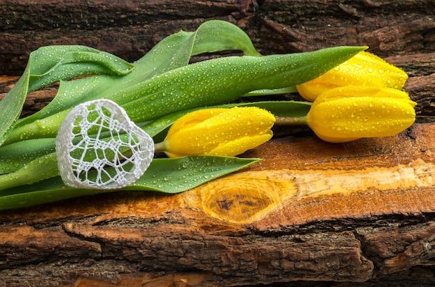 天然木の板に水滴が付いた新鮮な黄色のチューリップ。