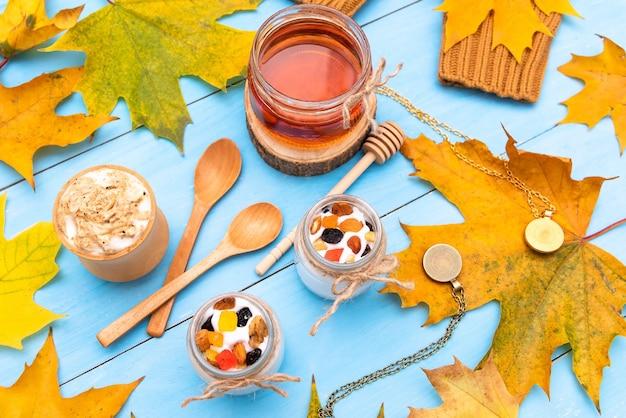 Свежий йогурт и мед на осеннем столе.