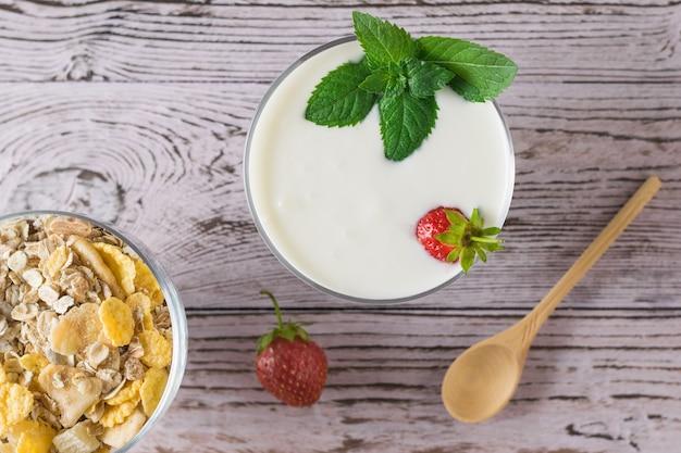 ピンクのテーブルの上に木のスプーンで新鮮なヨーグルトとオートミール。美味しくて健康的で栄養価の高い自然食品。上からの眺め。