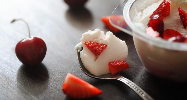 ベリー入りのフレッシュヨーグルト。新鮮でジューシーなイチゴとチェリーの入ったボウルにアイスクリーム。赤いベリーのデザート。