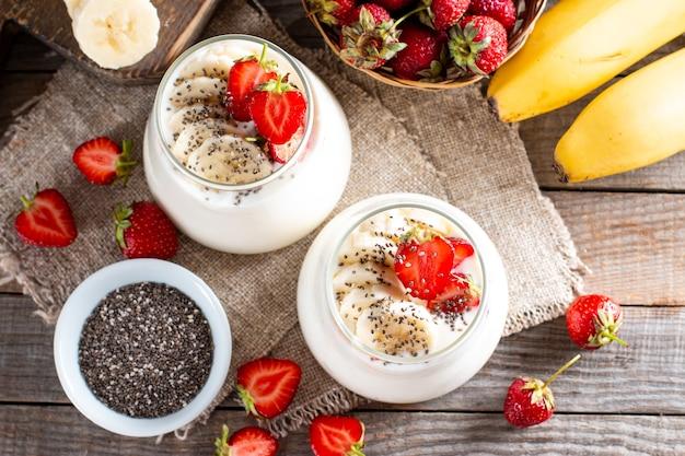 Свежий йогурт с клубникой, бананом, семенами чиа на деревянном столе, вкусный десерт для здорового завтрака. вид сверху