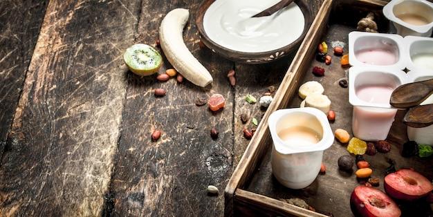 Свежие йогурты с фруктами и орехами. на деревянном фоне.