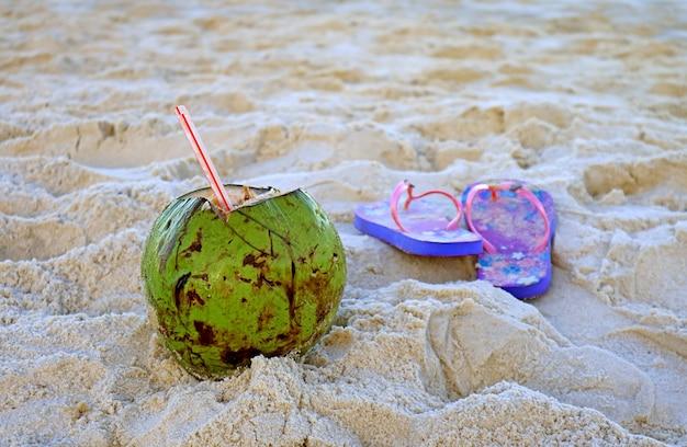 砂浜のぼやけたサンダルと新鮮な若いココナッツドリンク