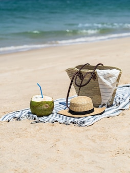 A fresh young coconut is ready to eat and a straw bag and a women's straw hat on a towel on  sandy beach against a blue sea. tropical vacation travel concept. copy space