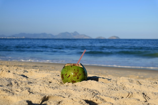 Fresh young coconut on the sandy beach copacabana in rio de janeiro, with blurred atlantic ocean in background