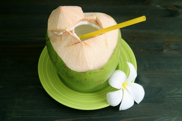 Fresh young coconut with yellow straw and plumeria flower served on green plate ready for drinking