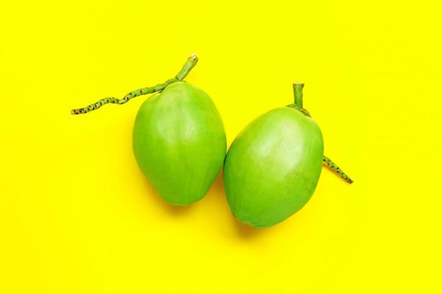 Свежие молодые кокосы на желтой поверхности.