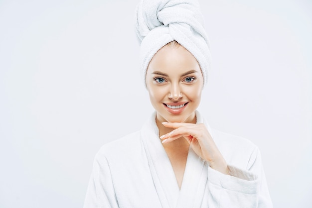 Fresh young european woman wears bath towel and robe, touches chin gently, spends free time in spa, undergoes beauty treatments after shower white background.