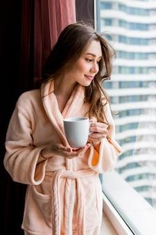 ピンクの柔らかいバスローブで新鮮な若い女性は、窓の外を見てお茶を飲みます。