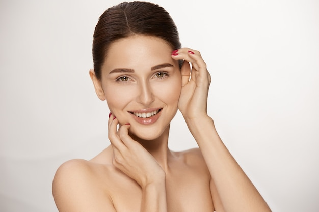 Fresh young woman smiling and touching her face with arms, perfect model with beautiful skin and shiny browm hair