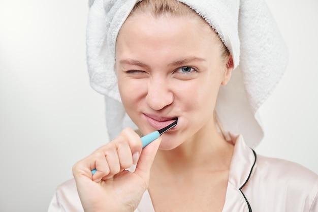 격리 아침 샤워 후 욕실에서 그녀의 이빨을 닦고 머리에 수건으로 신선한 젊은 여자