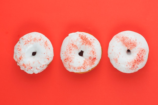 Fresh yummy white chocolate donuts on red background