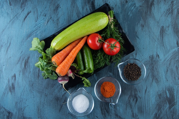 Zucchine fresche, carote, pomodori e verdure su banda nera con spezie.