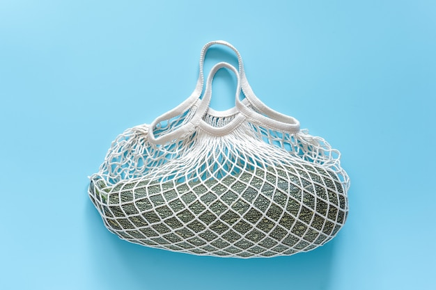 Fresh zucchini in reusable shopping eco-friendly mesh bag on blue background