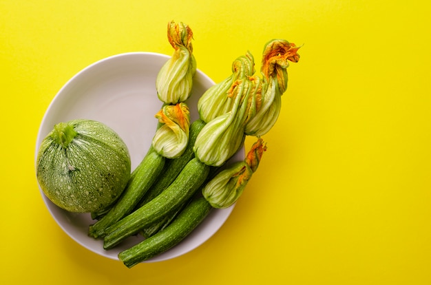 Fresh zucchini with flowers in a white bowl on bright yellow background