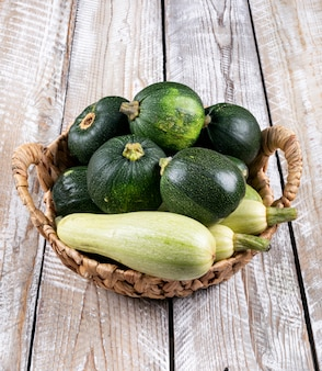 Fresh zucchinis in a basket on a light wooden table