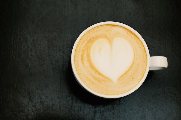 木製テーブルの上の柔らかい泡と心とfreshれたてのカプチーノの大きなカップのトップビュー。