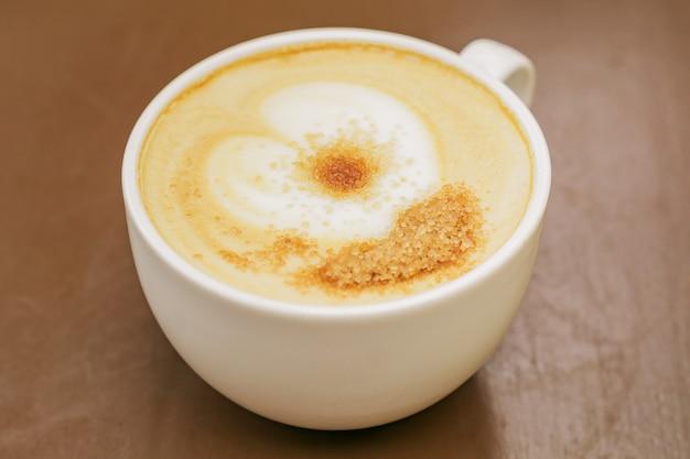 木製テーブルの上の柔らかい泡とブラウンシュガーとfreshれたてのカプチーノの大きなカップのクローズアップ。