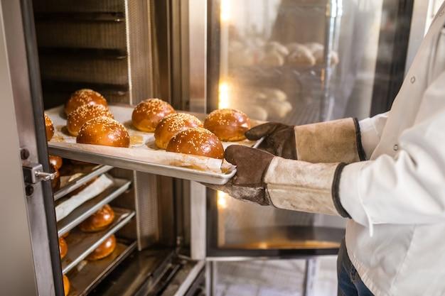 가장 신선한 빵. 빵집의 오븐에서 기성품 맛있는 롤을 얻는 특수 장갑에 남성 손