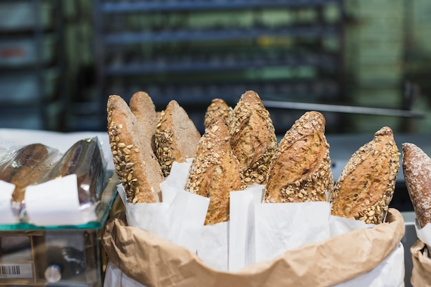 Freshly baguette baked bread in paper with different seeds