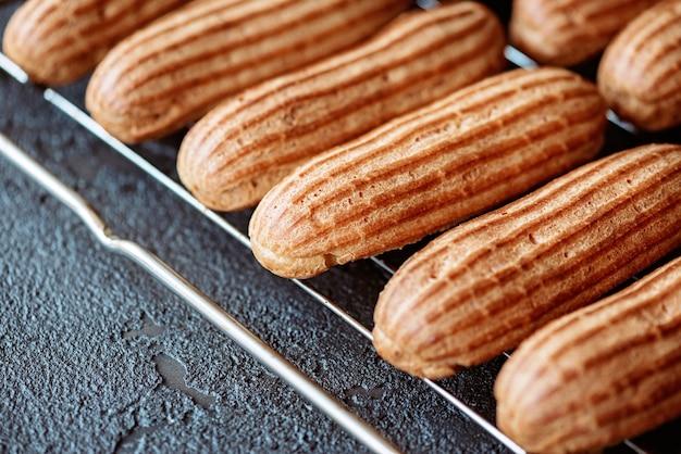 焼きたてのアロマカスタードケーキは、暗い質感の背景のワイヤーラックで涼しくなります