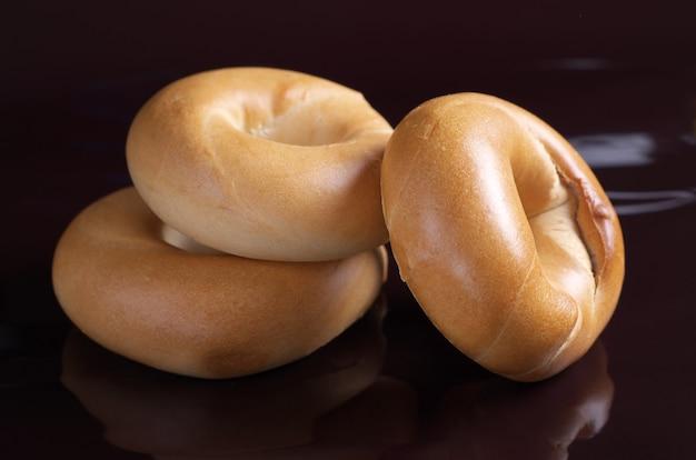 Freshly baked bagels on black background close up
