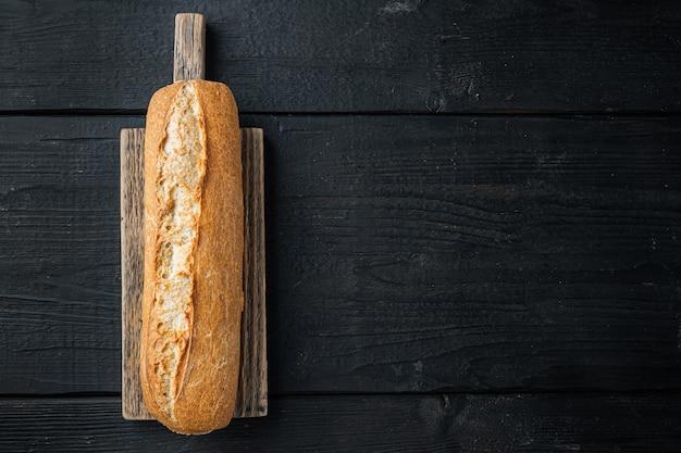 Freshly baked baguette, on black wooden table
